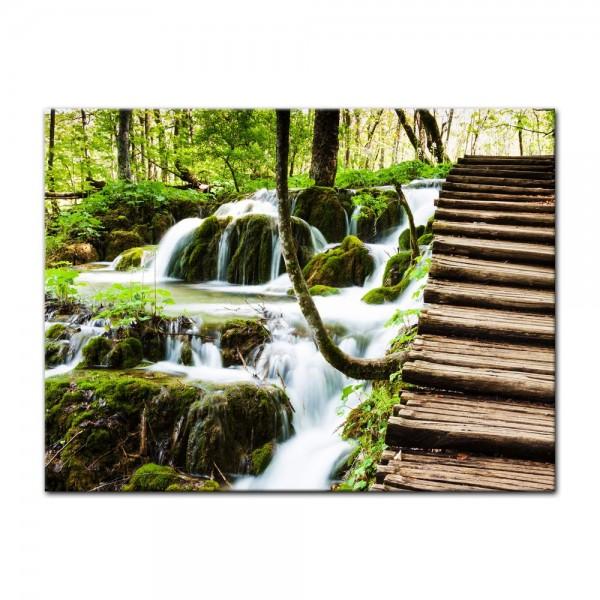 Leinwandbild - Holzbrücke über einem Wasserfall